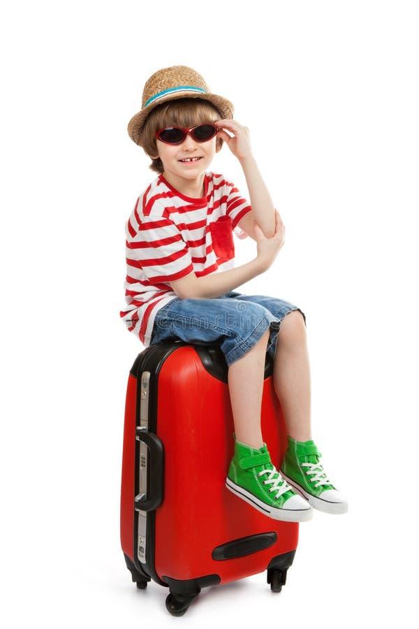 Le garçon avec des lunettes de soleil s'assied sur la valise photos libres de droits