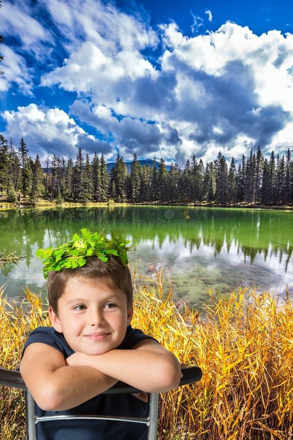 Le garçon avec du charme s'assied sur le rivage du petit lac photos stock
