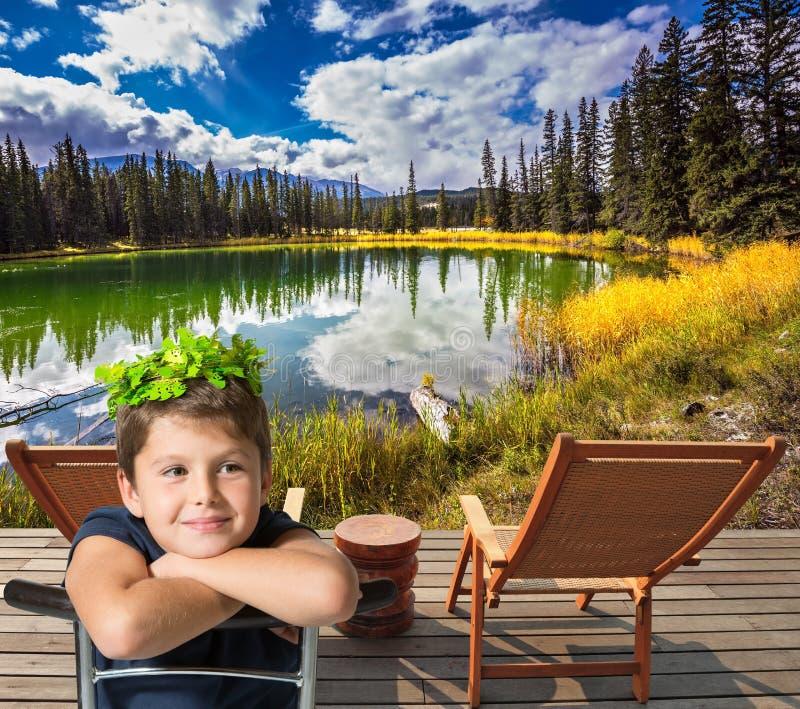 Le garçon avec du charme s'assied sur le petit lac circulaire photo stock