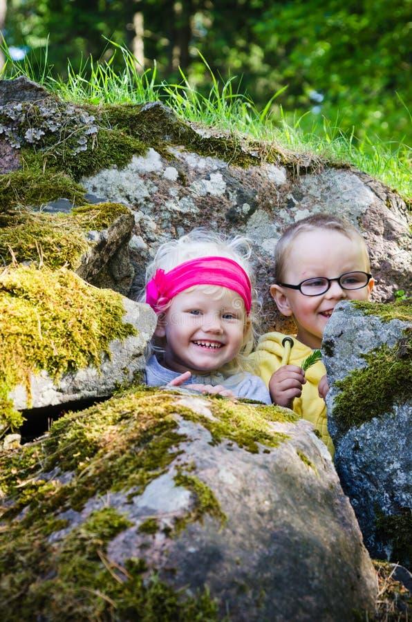le garçon avec la fille s'est caché parmi les roches photo libre de droits