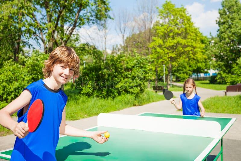 Le garçon avec la raquette sert la balle de tennis de table à la fille images libres de droits