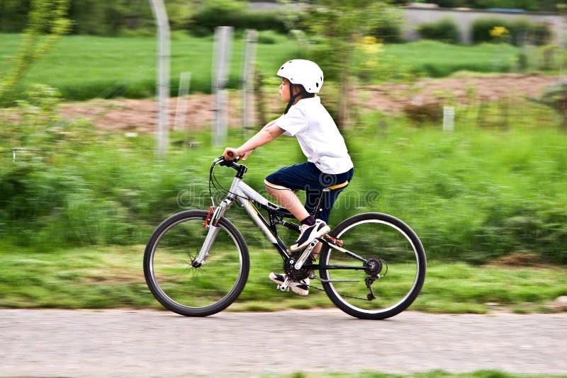 Le garçon avec le casque monte le vélo de montagne photo libre de droits