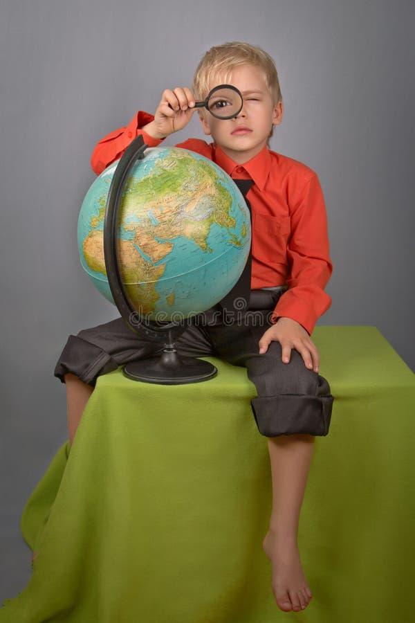 Le garçon avec le globe et une loupe. photos stock