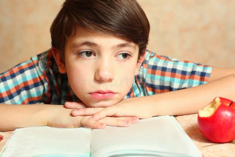 Le garçon avec le livre et la pomme pensent photo stock
