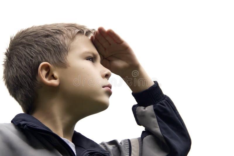Le garçon avec un visage fier examine la distance image stock