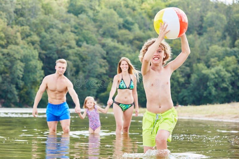 Le garçon avec une boule joue hilare en mer photographie stock libre de droits