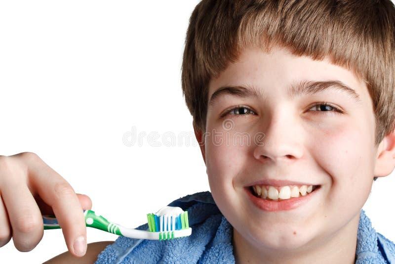 Le garçon avec une brosse à dents. image stock