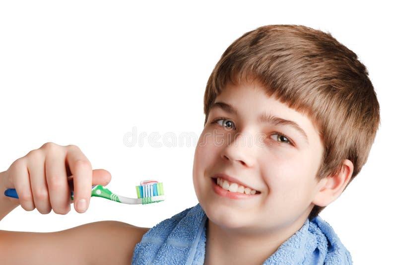 Le garçon avec une brosse à dents. photos stock