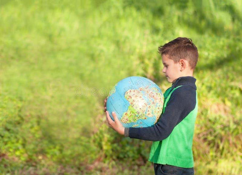 Le garçon beau tient un globe Élève en parc, étude image stock