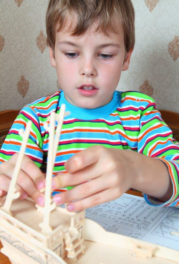 Le garçon blond ardent effectuent le bateau en bois fait maison image stock