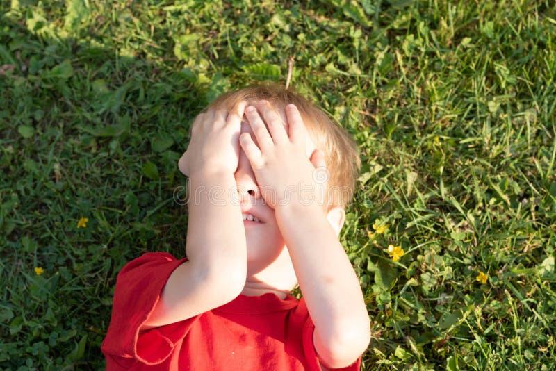 Le garçon blond européen a fermé ses yeux avec ses mains se trouvant sur l'herbe photographie stock libre de droits