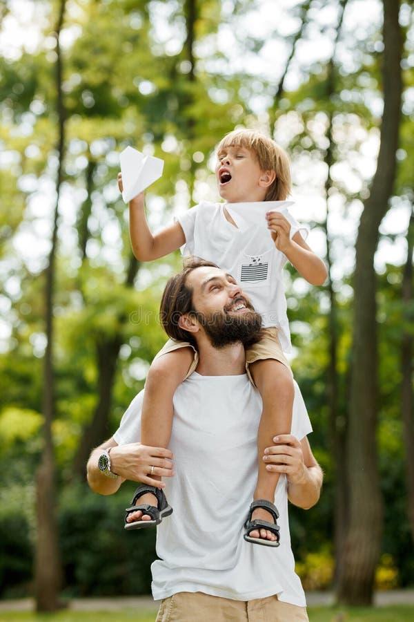 Le garçon blond utilisant un T-shirt blanc se reposant sur les épaules de son père barbu beau et garde un avion de papier dedans images libres de droits