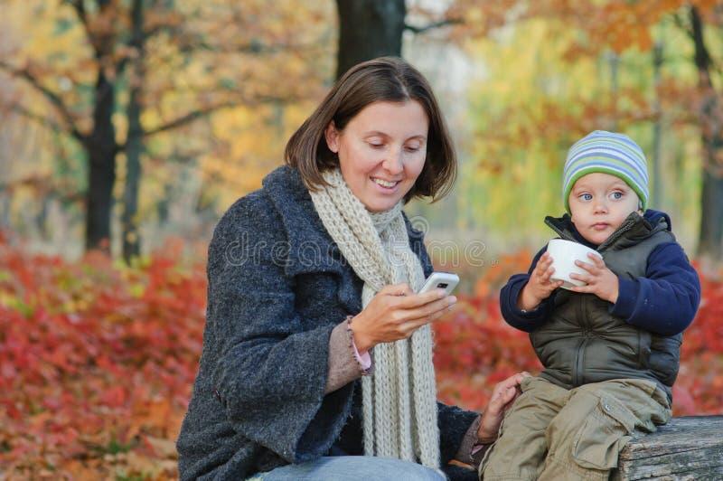 Le garçon boit du thé avec sa mère images libres de droits