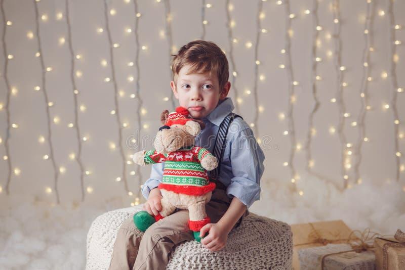 le garçon caucasien blanc de renversement triste tenant des orignaux de cerfs communs jouent célébrer Noël ou la nouvelle année image stock