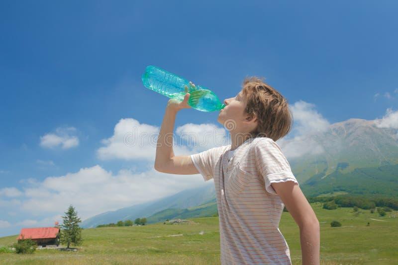 Le garçon caucasien buvant l'eau claire de la bataille dans le sien remet la haute dans les Alpes images libres de droits