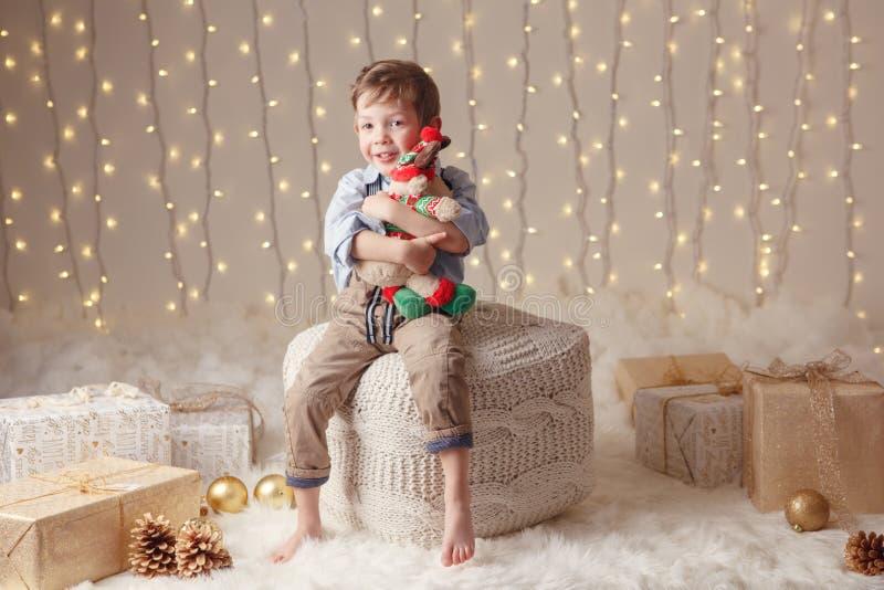 Le garçon caucasien tenant des orignaux de cerfs communs jouent célébrer Noël ou la nouvelle année photographie stock