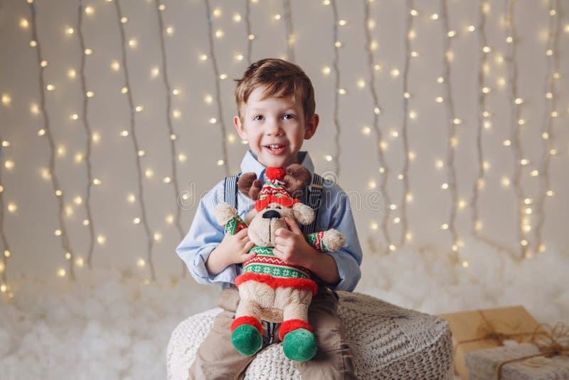 Le garçon caucasien tenant des orignaux de cerfs communs jouent célébrer Noël ou la nouvelle année photo stock