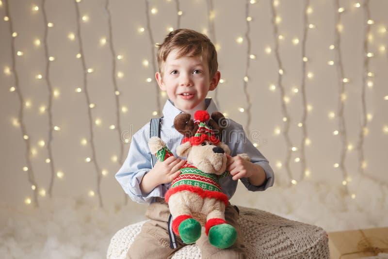 Le garçon caucasien tenant des orignaux de cerfs communs jouent célébrer Noël ou la nouvelle année images stock