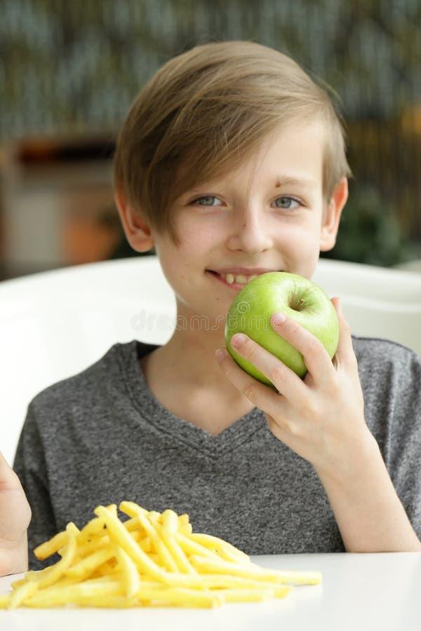 Le garçon choisit le fruit ou les aliments de préparation rapide images libres de droits