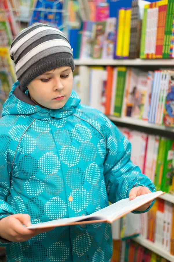 Le garçon choisit un livre dans la boutique images stock