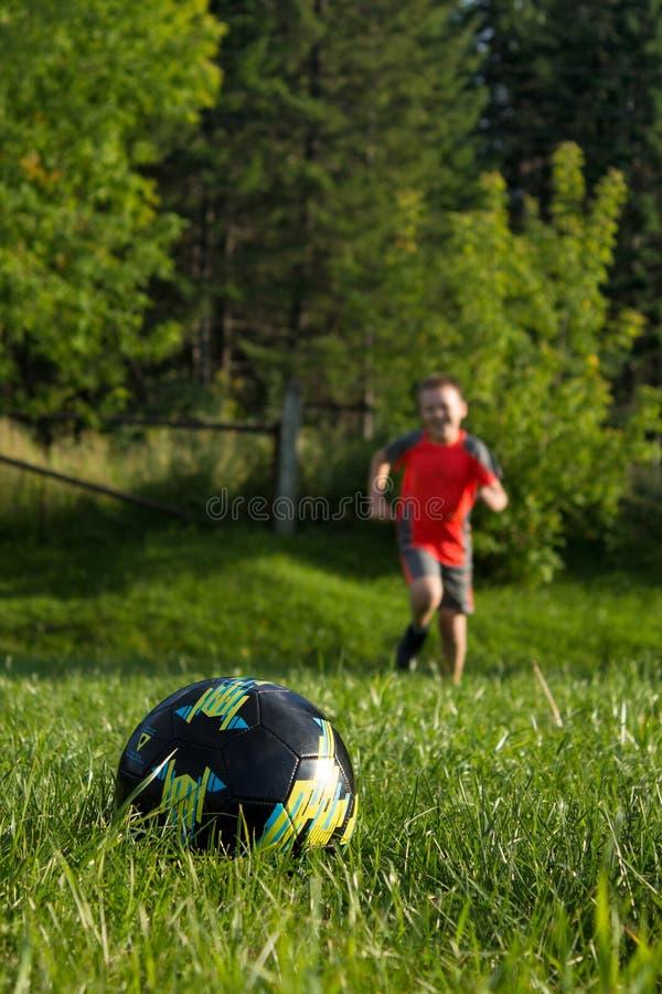 Le garçon court à la boule images stock