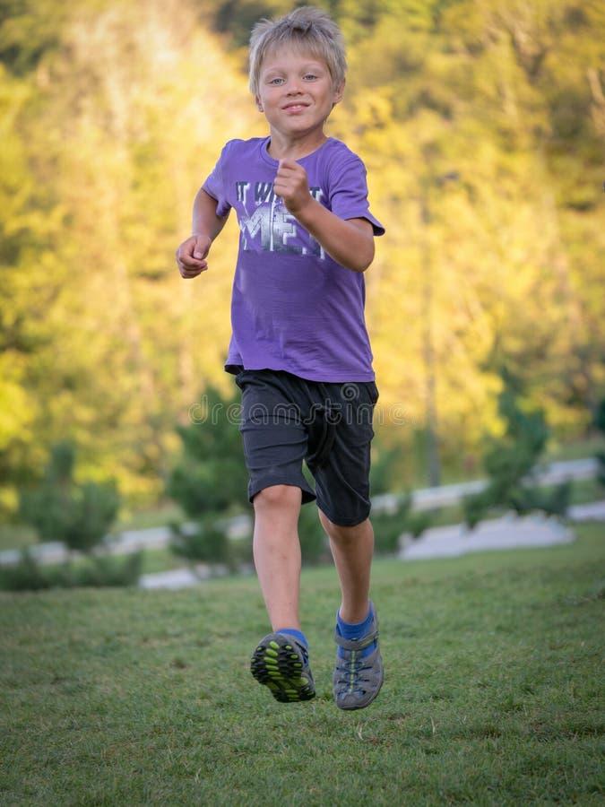 Le garçon court rapidement sur la pelouse verte images libres de droits