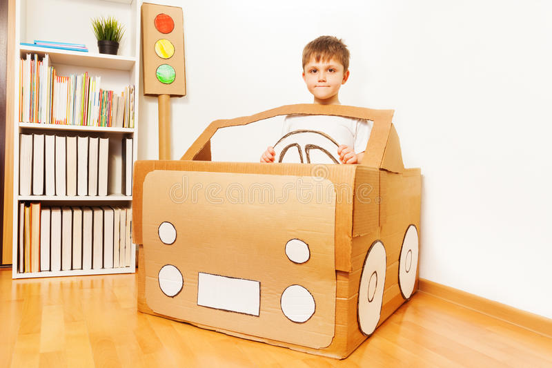 Le garçon créatif d'enfant joue avec sa voiture de carton photographie stock