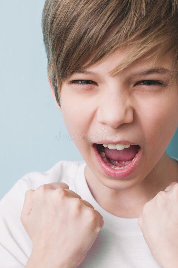 Le garçon crie et démontre ses poings dans le geste victorieux images stock
