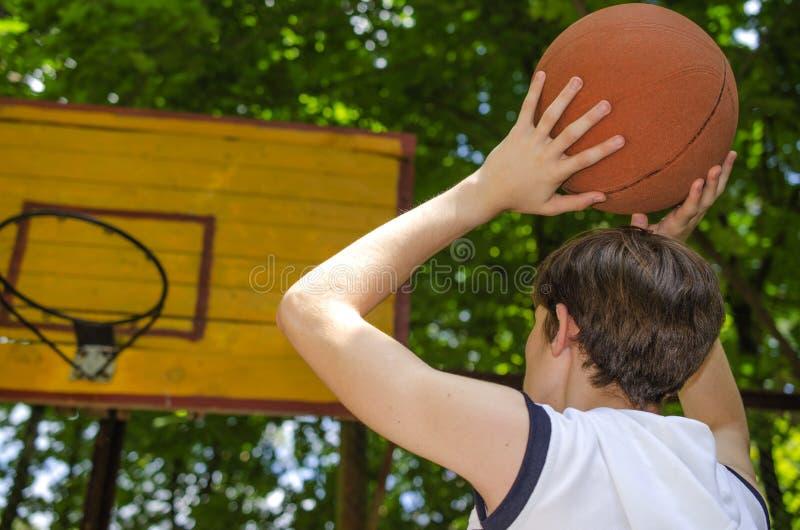 Le garçon d'adolescent avec une boule pour le basket-ball joue le basket-ball photos stock