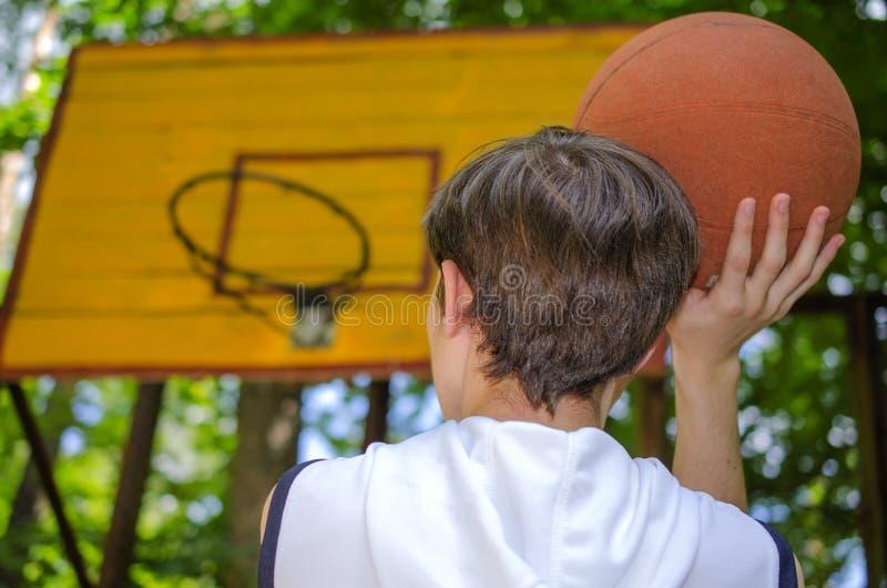 Le garçon d'adolescent avec une boule pour le basket-ball joue le basket-ball images stock