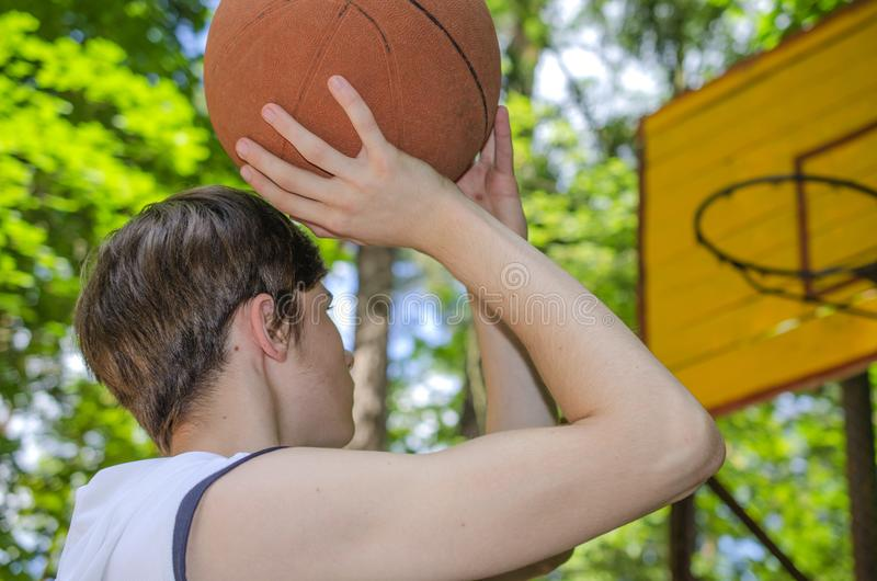 Le garçon d'adolescent avec une boule pour le basket-ball joue le basket-ball photographie stock