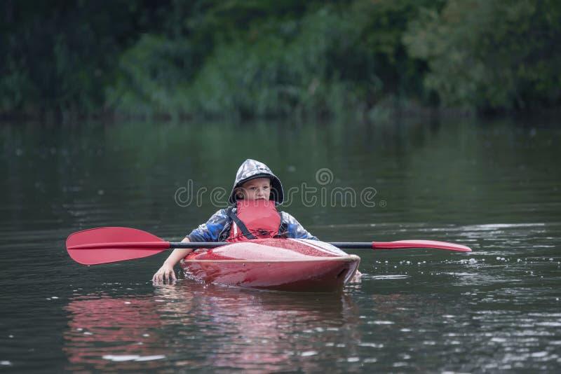 Le garçon d'adolescent dans un kayak de bateau de queue a mis son aviron sur le bateau et le Ti image stock