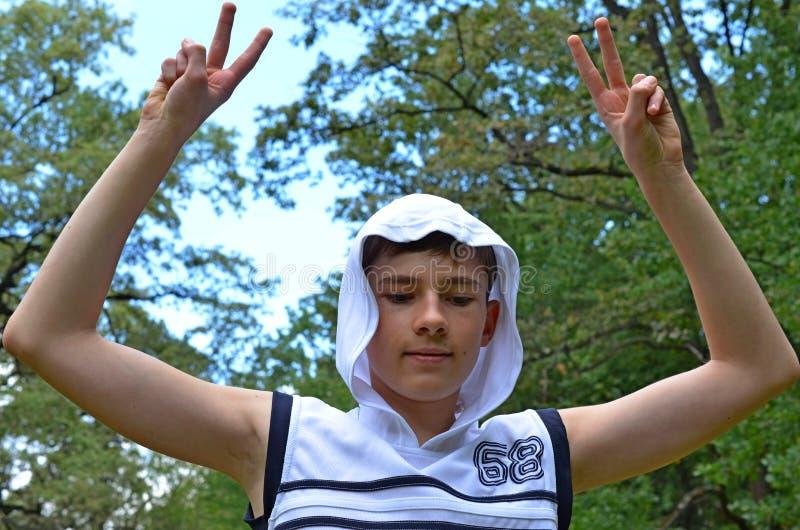 Le garçon d'adolescent dans une chemise blanche sans douilles avec des mains a tendu dans un geste de victoire photographie stock