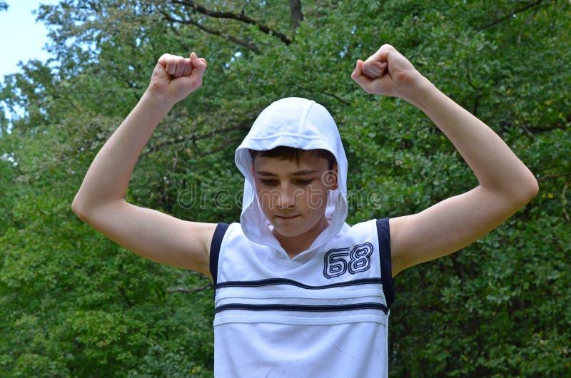Le garçon d'adolescent dans une chemise blanche sans douilles avec des mains a tendu dans un geste de victoire image stock
