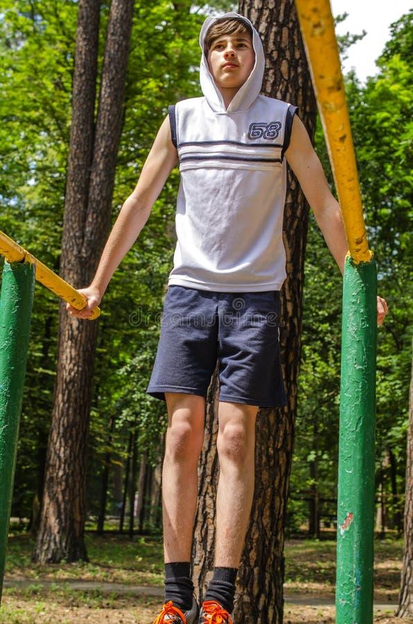 Le garçon d'adolescent fait des exercices physiques sur des barres parallèles photos stock