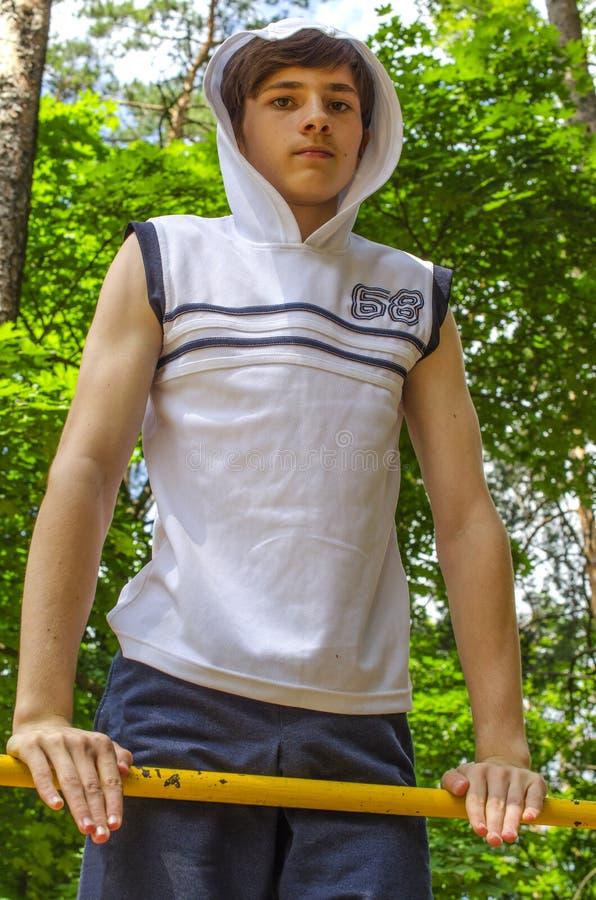Le garçon d'adolescent tire vers le haut sur une barre horizontale photo stock