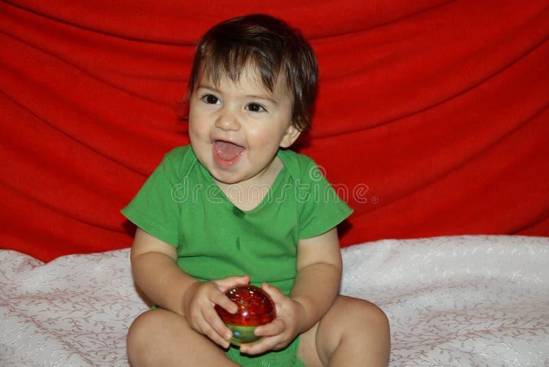 le garçon d'amusement que le bébé rit heureusement des jeux tient la boule en verre de Noël images libres de droits