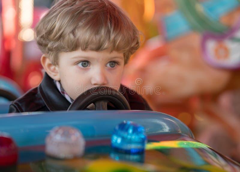 Le garçon d'enfant conduit une voiture bleue au carrousel photographie stock libre de droits