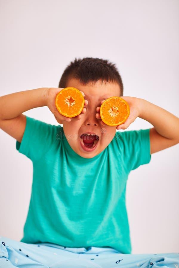 Le garçon d'enfant dans la chemise de turquoise, ouverte sa bouche et prises deux a coupé l'orange à la hauteur d'oeil - fruit et photos libres de droits