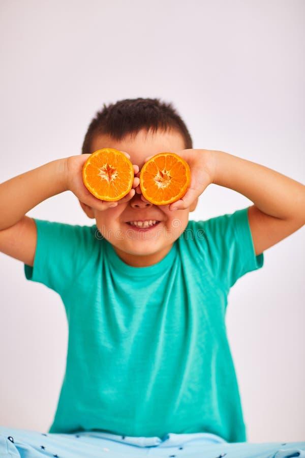 Le garçon d'enfant dans une chemise de turquoise, souriant et tenant deux a coupé l'orange à la hauteur d'oeil - fruit et nourrit photos libres de droits