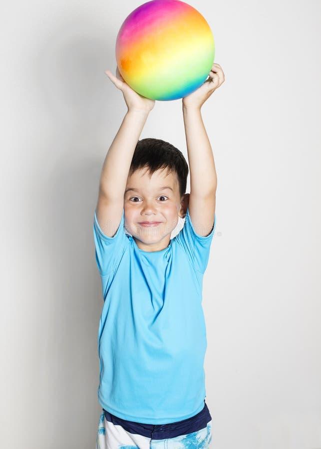 Le garçon d'enfant en bas âge s'est habillé dans un T-shirt avec le filtre UV avec la boule d'arc-en-ciel photographie stock