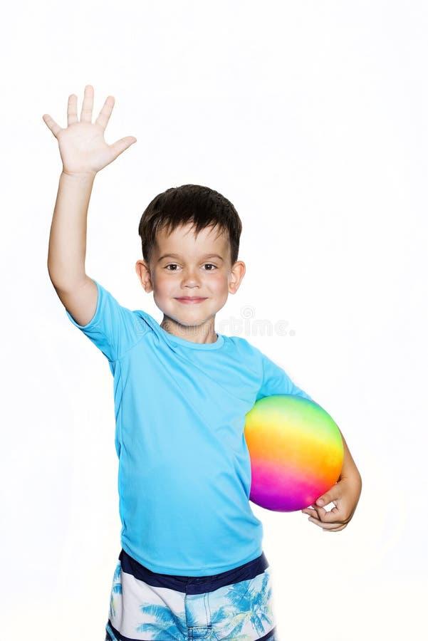 Le garçon d'enfant en bas âge s'est habillé dans un T-shirt avec le filtre UV avec la boule d'arc-en-ciel images stock