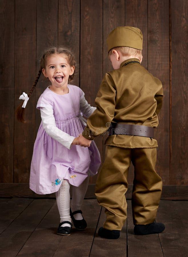 Le garçon d'enfants sont habillés comme soldat dans de rétros uniformes militaires et fille dans la robe rose photographie stock