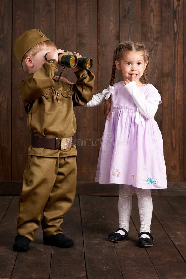 Le garçon d'enfants sont habillés comme soldat dans de rétros uniformes militaires et fille dans la robe rose image libre de droits