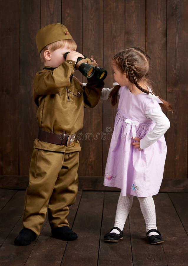 Le garçon d'enfants sont habillés comme soldat dans de rétros uniformes militaires et fille dans la robe rose image stock