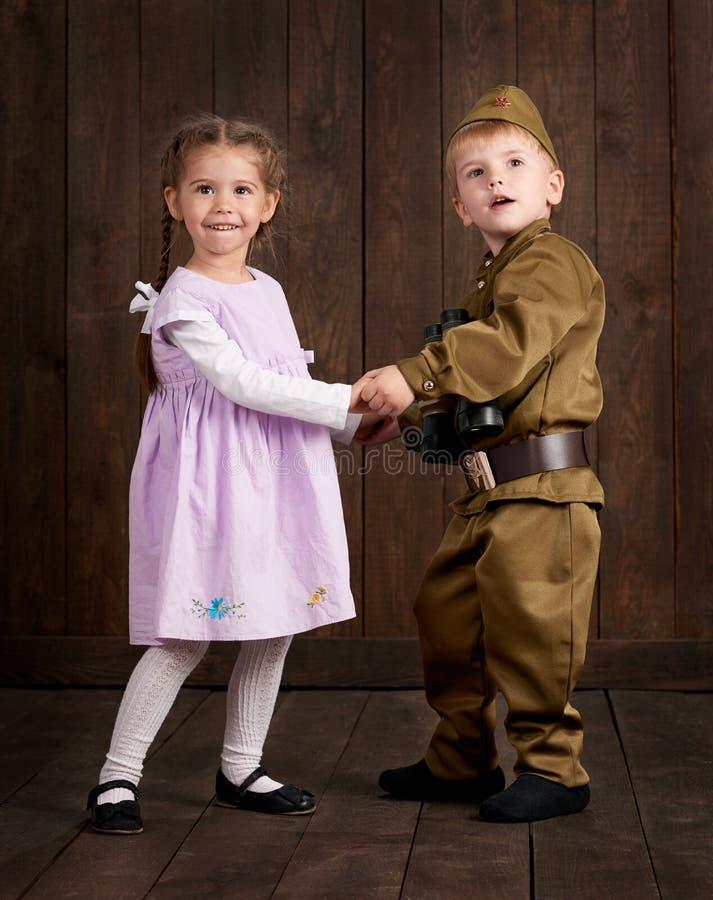 Le garçon d'enfants sont habillés comme soldat dans de rétros uniformes militaires et fille dans la robe rose images stock