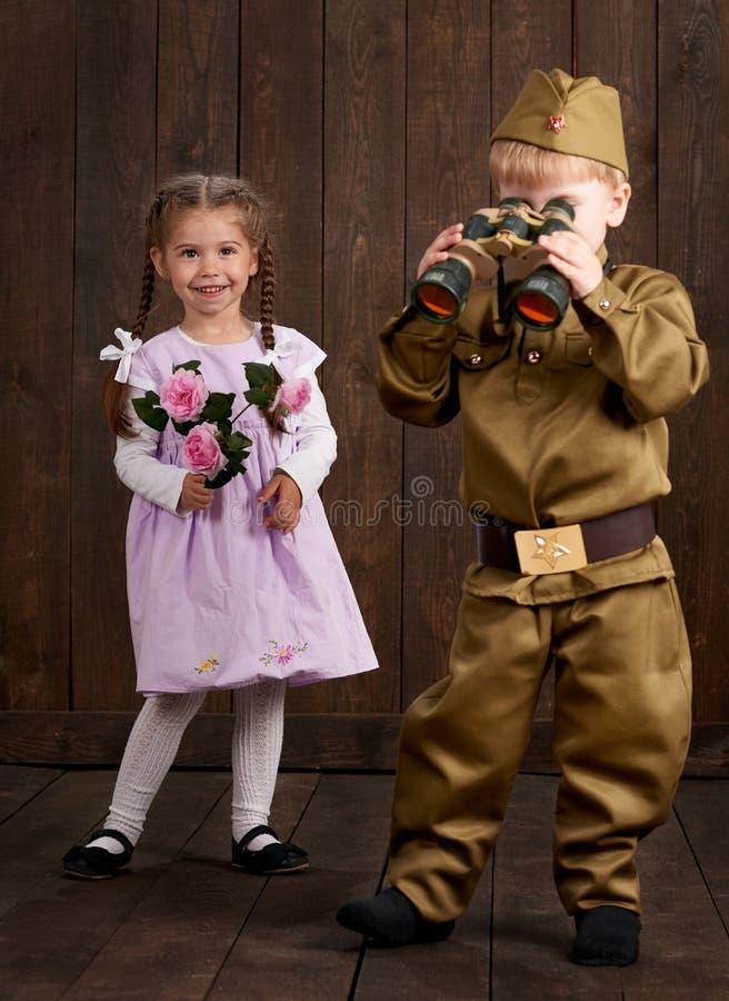Le garçon d'enfants sont habillés comme soldat dans de rétros uniformes militaires et fille dans la robe rose photographie stock libre de droits