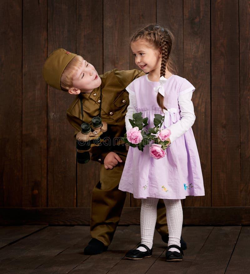Le garçon d'enfants sont habillés comme soldat dans de rétros uniformes militaires et fille dans la robe rose images libres de droits