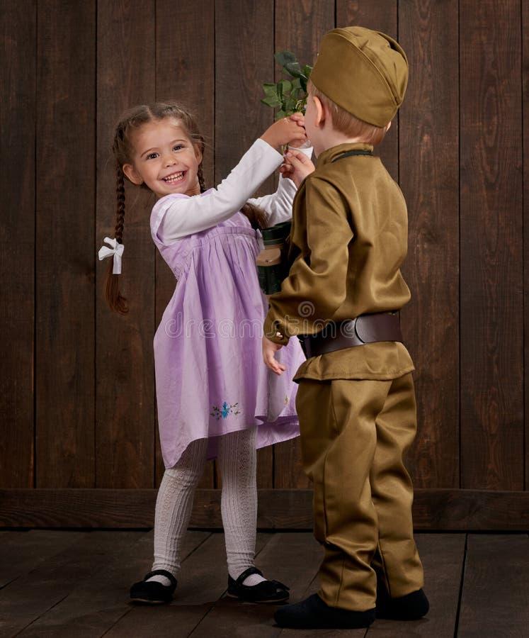 Le garçon d'enfants sont habillés comme soldat dans de rétros uniformes militaires et fille dans la robe rose photo stock