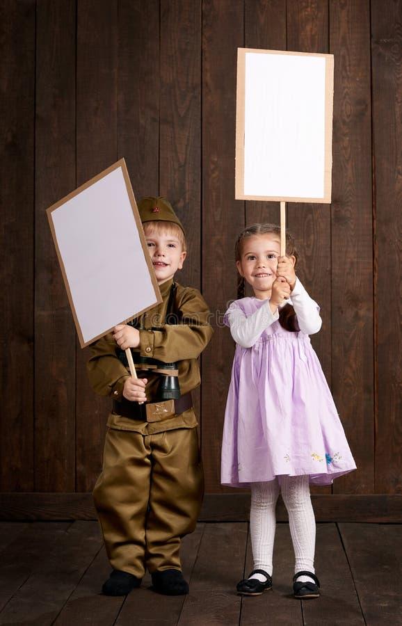 Le garçon d'enfants sont habillés comme soldat dans de rétros uniformes militaires et fille dans la robe rose Ils ` au sujet de t images stock